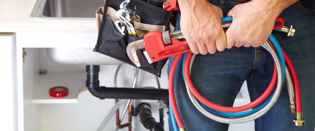 Plumber holding hoses and tools