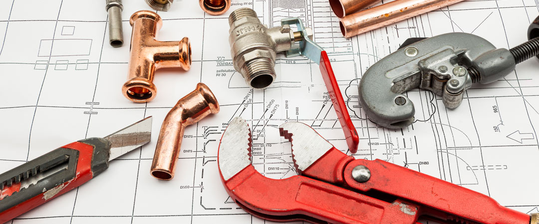 Plumbing tools and supplies on top of house plans