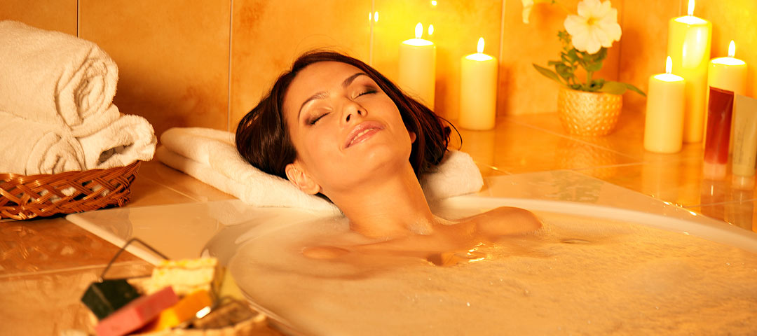 Lady soaking in a bubble bath surrounded with candles