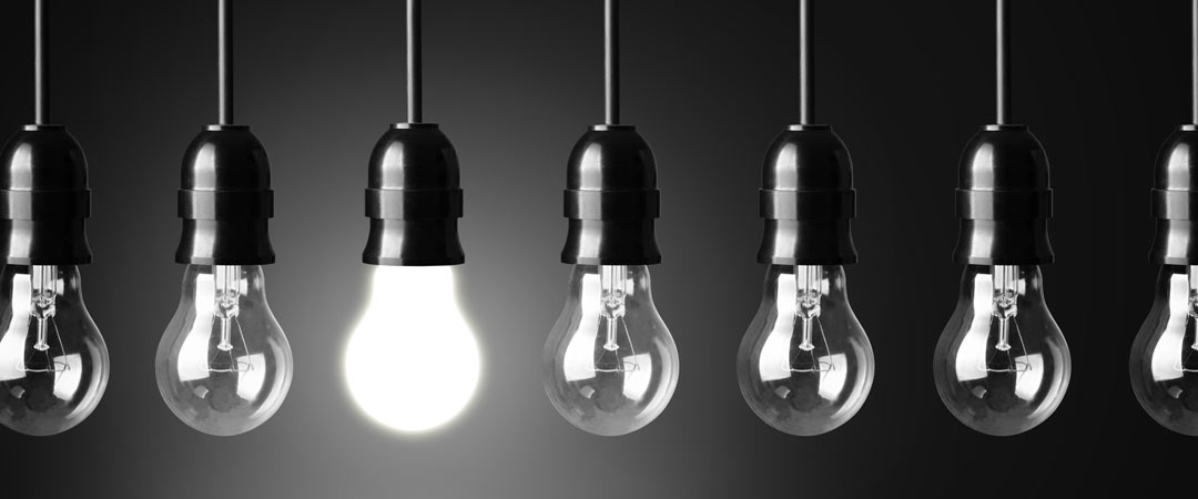 Light bulbs a row with one lit