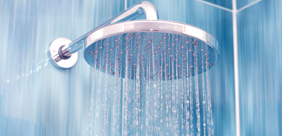 Silver shower head in a blue shower