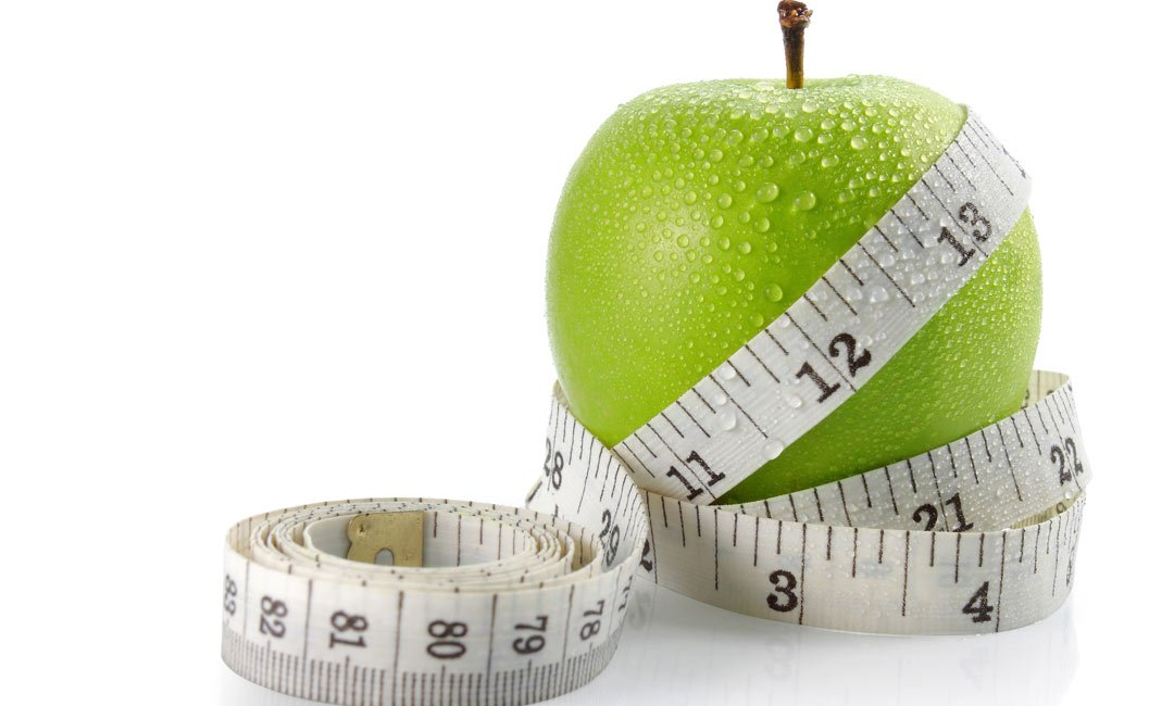 Green apple with a tape measure