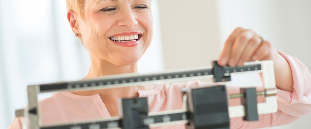 Smiling woman adjusting a weight scale