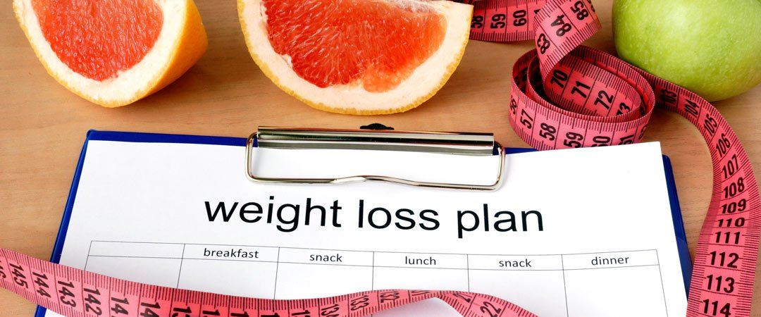 Weight loss plan on a clipboard with fruits and tape measure