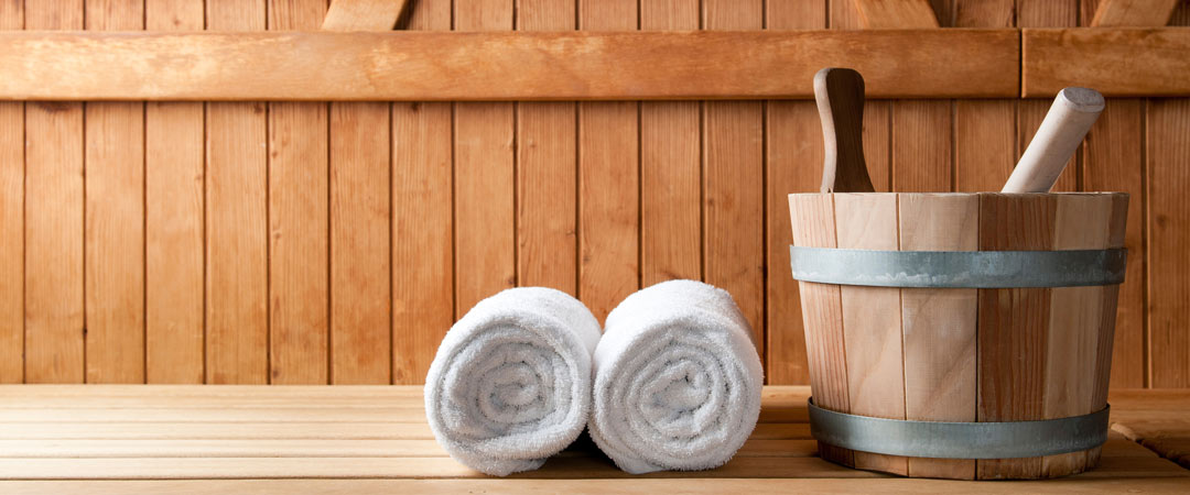 Rolled towels on a sauna bench with a bucket of water