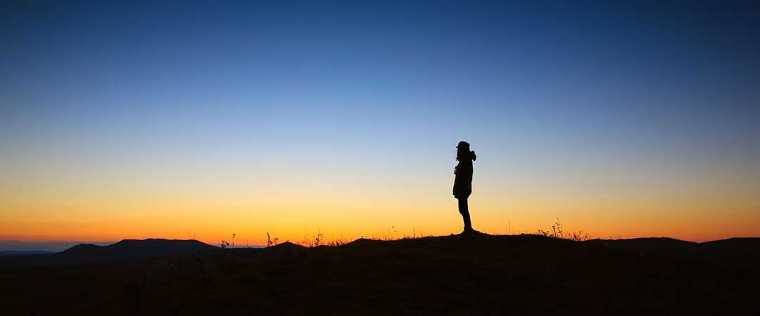 Woman standing in a field watching the sunset