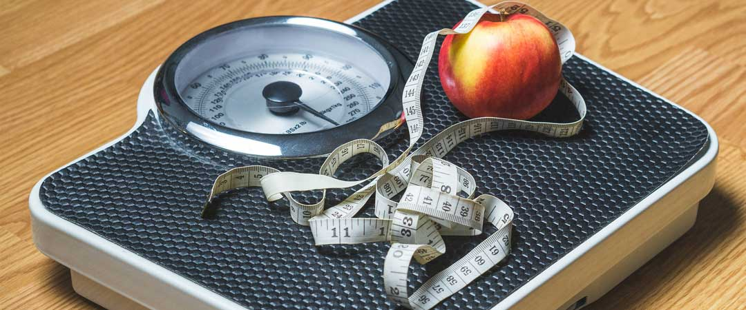 Scale with tape measure and apple