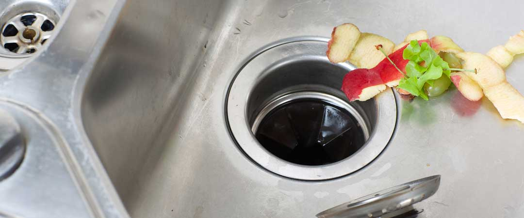 Kitchen sink with food debris going into garbage disposal splash guard